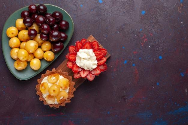 Vista dall'alto di piccole torte cremose con frutta a fette e ciliegie fresche sulla superficie scura