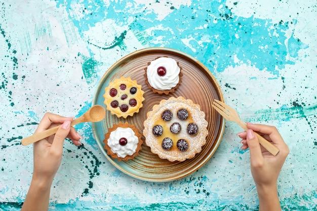 Vista dall'alto piccole torte cremose con frutta zucchero in polvere sullo sfondo azzurro torta crema cuocere dolce