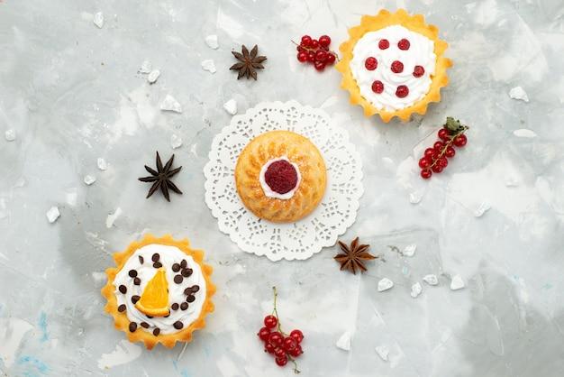 Вид сверху маленькие торты со сливками и разными фруктами, изолированные на светлой поверхности, сахар, сладкий чай