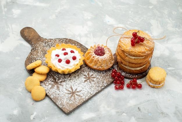 Vista dall'alto piccole torte d con panna e biscotti sulla superficie leggera zucchero dolce
