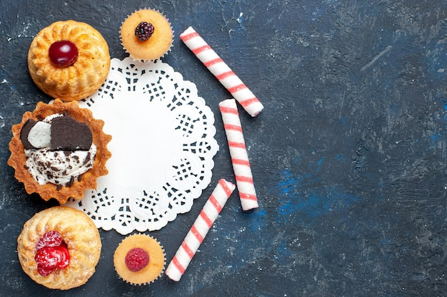 トップビュー暗い背景にクッキーとピンクのスティックキャンディーフルーツと一緒に少しおいしいケーキビスケットケーキ甘いフルーツ焼き