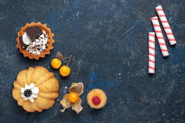 Вид сверху маленький вкусный торт вместе с печеньем и розовыми конфетами на темном фоне бисквитный торт сладкие фрукты