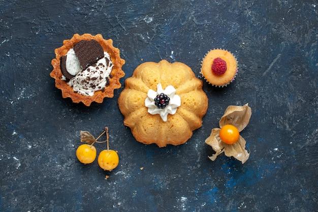 Вид сверху маленький вкусный торт вместе с печеньем на темном фоне бисквитный торт сладкие фрукты