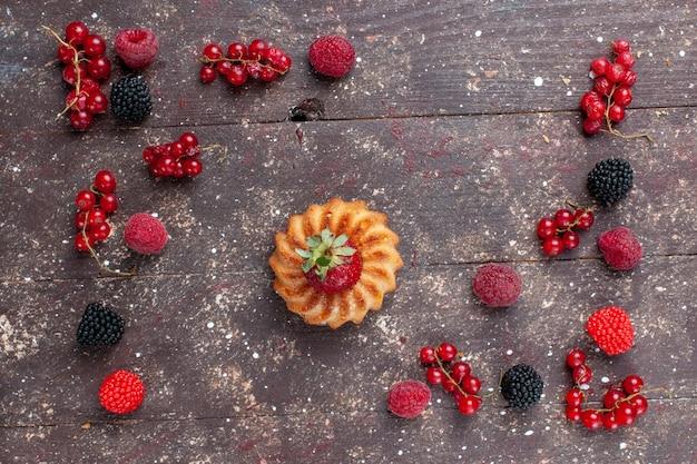 Вид сверху маленький вкусный торт вместе с разноцветными ягодами, разложенными по коричневому столу, ягодно-фруктовый бисквит