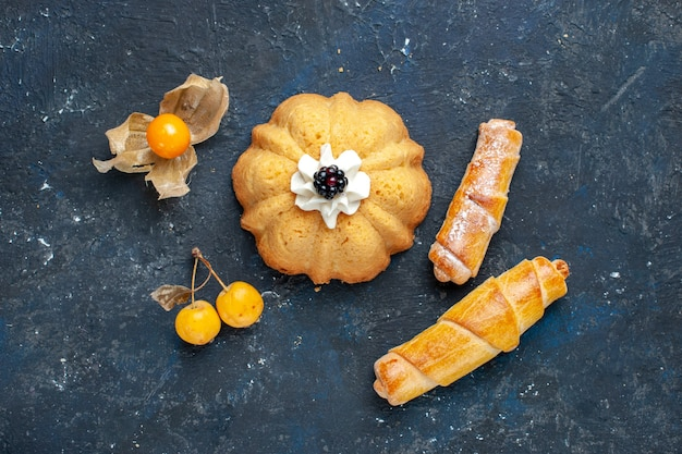 Vista dall'alto piccola torta deliziosa insieme a braccialetti dolci sulla frutta dolce torta biscotto scuro scrivania