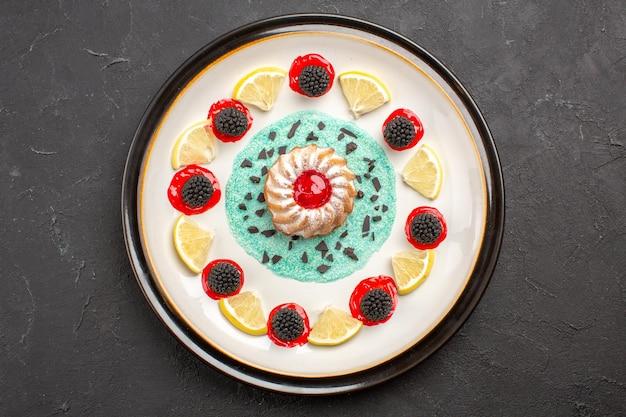 暗い背景のプレートの内側にコンフィチュールとレモンスライスが入った小さなおいしいケーキの上面図フルーツシトラスクッキービスケットスイート