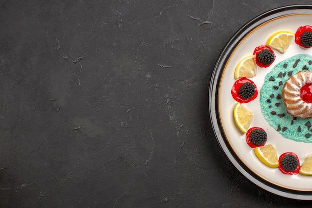 Vista dall'alto piccola deliziosa torta con confetture e fette di limone all'interno del piatto su un dolce biscotto agli agrumi da scrivania scuro