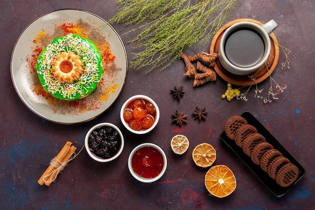 Вид сверху маленький вкусный торт с печеньем и чаем на темной поверхности