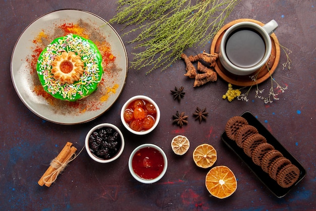 Vista dall'alto piccola deliziosa torta con biscotti e tè sulla superficie scura