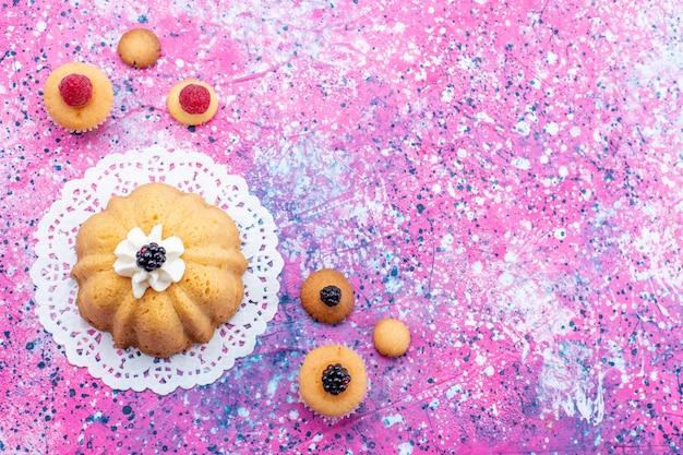 Vista dall'alto piccola deliziosa torta con crema e frutti di bosco sulla luminosa scrivania torta biscotto bacca dolce zucchero foto