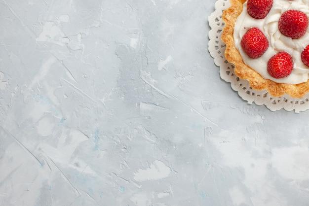 トップビュー灰白色のデスクケーキフルーツベリービスケットスイートクリームにクリームと新鮮な赤いイチゴの小さなおいしいケーキ