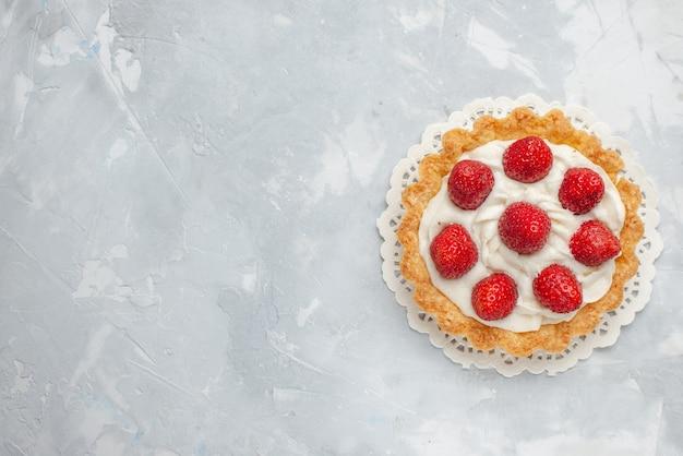 Вид сверху маленький вкусный торт со сливками и свежей красной клубникой на светлом фоне торт фруктово-ягодный бисквитный сладкий крем