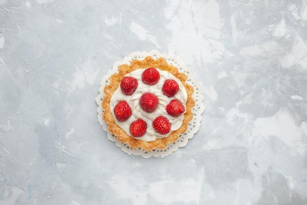 Вид сверху маленький вкусный торт со сливками и свежей красной клубникой на светлом столе торт фруктовые ягоды бисквитный сладкий крем