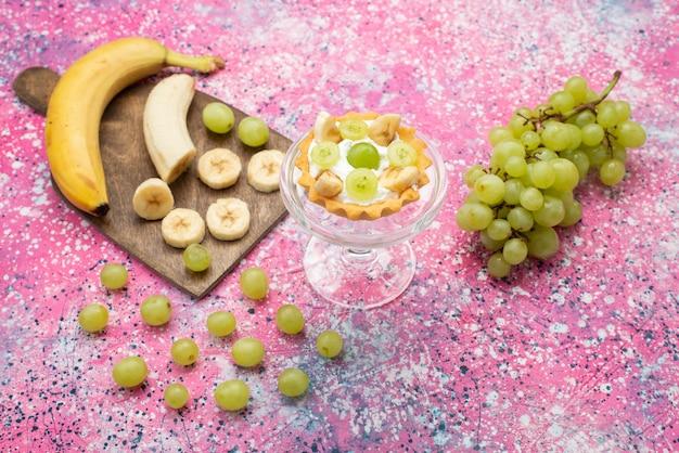 Вид сверху маленький вкусный торт со сливками и нарезанными бананами и виноградом на яркой поверхности фруктовой сладости