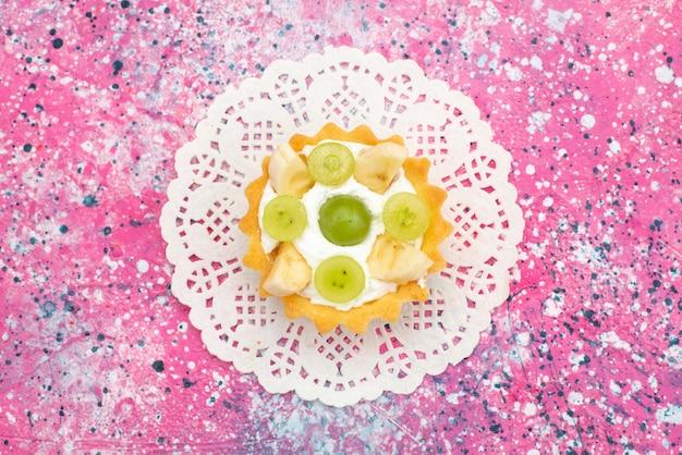 色付きの表面に甘いクリームとスライスされたフルーツの小さなおいしいケーキ