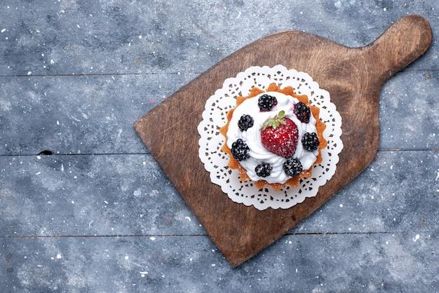 Vista dall'alto piccola deliziosa torta con crema e frutti di bosco sullo sfondo chiaro torta biscotto dolce foto cuocere la bacca