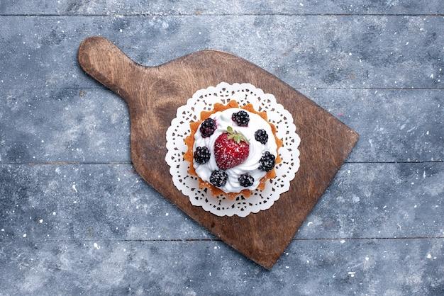 Vista dall'alto piccola deliziosa torta con crema e frutti di bosco sul tavolo luminoso torta biscotto dolce zucchero foto cuocere bacca