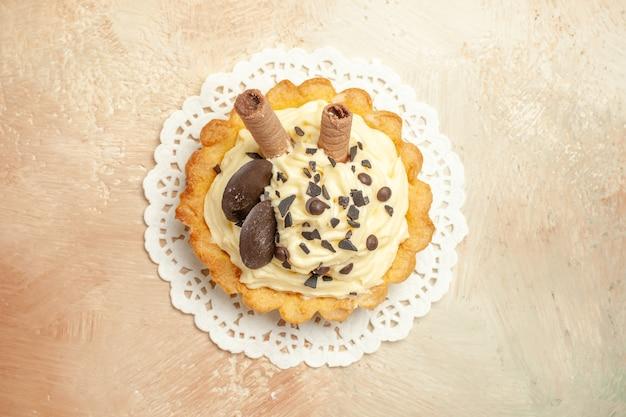 Вид сверху маленький вкусный торт со сливками на легком столе, торт, десерт, сладкий пирог