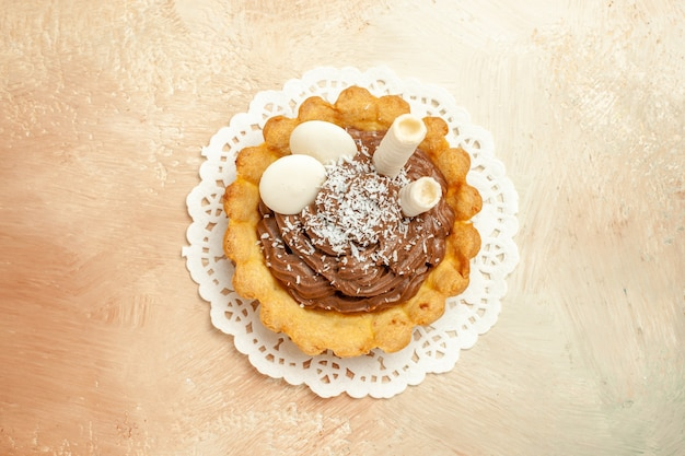 トップビューライトテーブルのパイケーキの甘いデザートにクリームと少しおいしいケーキ