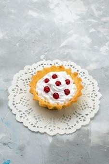 Vista dall'alto piccola deliziosa torta con crema e frutti rossi sulla superficie grigia dolce