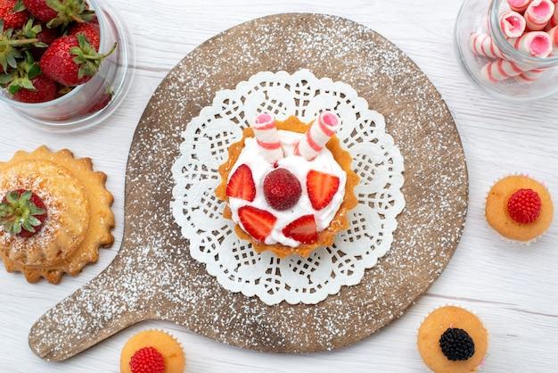 Vista dall'alto piccola deliziosa torta con crema e fette di fragole fresche rosse torte sul tavolo bianco torta bacca dolce cuocere infornare frutta cuocere