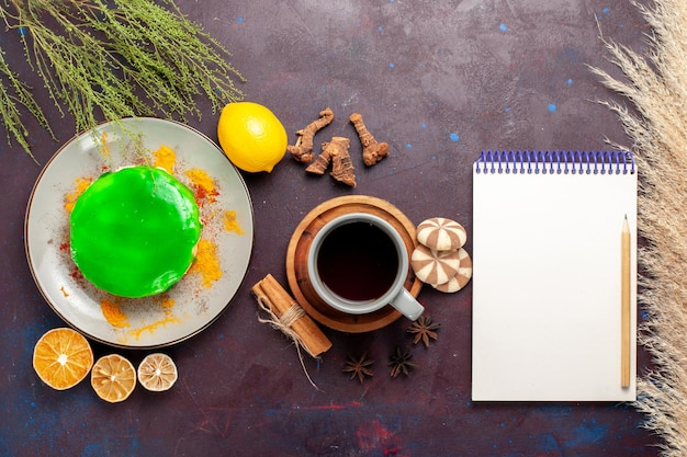 Vista dall'alto piccola deliziosa torta con una tazza di tè e biscotti su una superficie scura