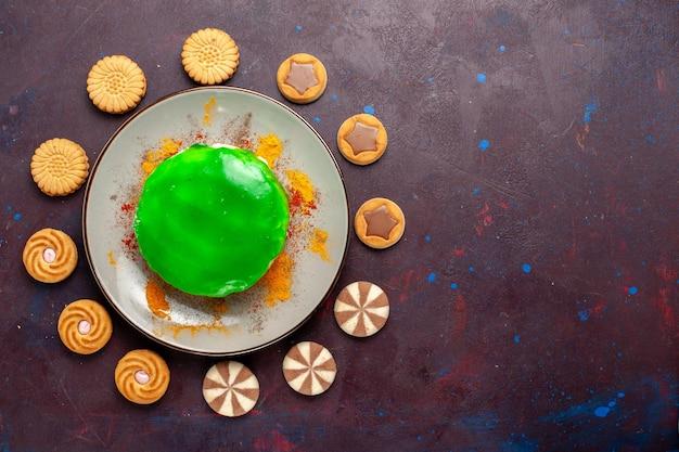 Vista dall'alto piccola deliziosa torta con diversi biscotti sulla superficie scura