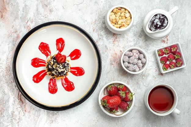 Вид сверху маленький вкусный торт с фруктами и чашкой чая на белой поверхности бисквитного печенья, сладкого печенья, пирога