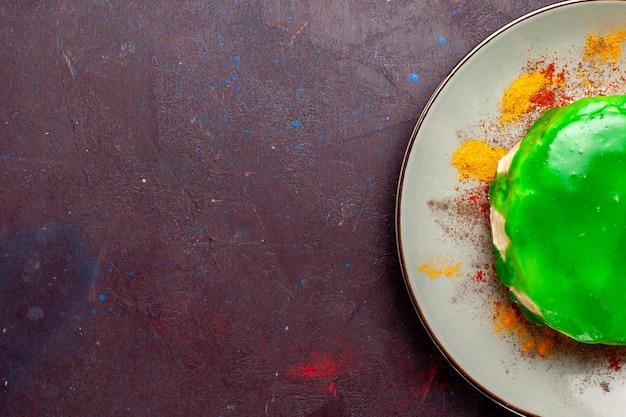 Vista dall'alto piccola deliziosa torta con crema verde sulla superficie scura