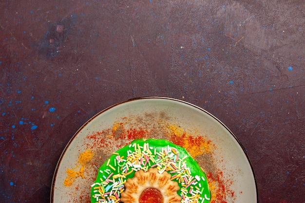 Vista dall'alto piccola deliziosa torta con crema verde all'interno del piatto sulla superficie scura
