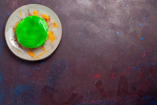어두운 책상 위에 있는 접시 안에 녹색 크림을 넣은 작은 맛있는 케이크