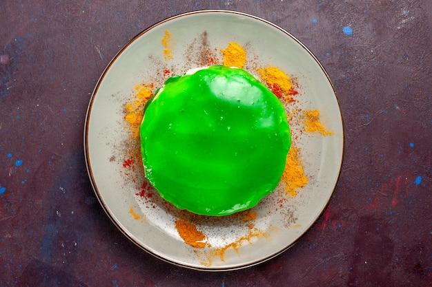 暗い表面のプレートの内側に緑色のクリームが入った上面図の小さなおいしいケーキ