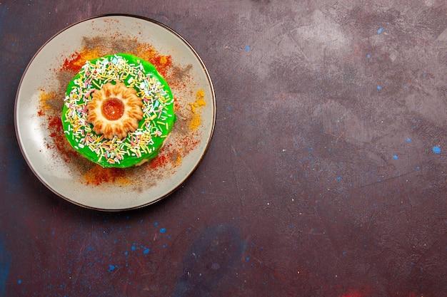 暗い机の上にグリーンクリームとトップビューの小さなおいしいケーキ