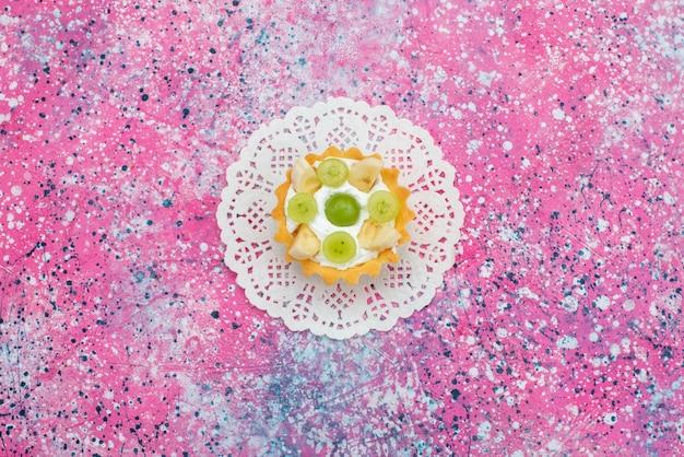 Vista dall'alto piccola deliziosa torta con kiwi e banane sul colore biscotto luminoso della scrivania