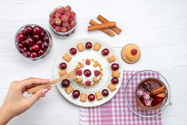 Вид сверху маленький вкусный торт с малиной, вишней и маленьким бисквитным чаем с корицей на светлом столе фруктовый ягодный крем-чай