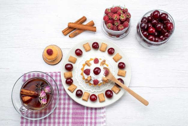 Вид сверху маленький вкусный торт с малиной, вишней и маленьким печеньем, чай с корицей на белом столе, фруктовый ягодный чай со сливками