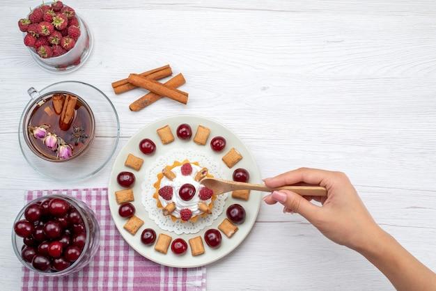 Vista dall'alto piccola deliziosa torta con lamponi, ciliegie e piccoli biscotti, tè alla cannella sulla scrivania bianca, frutta bacca, crema di tè