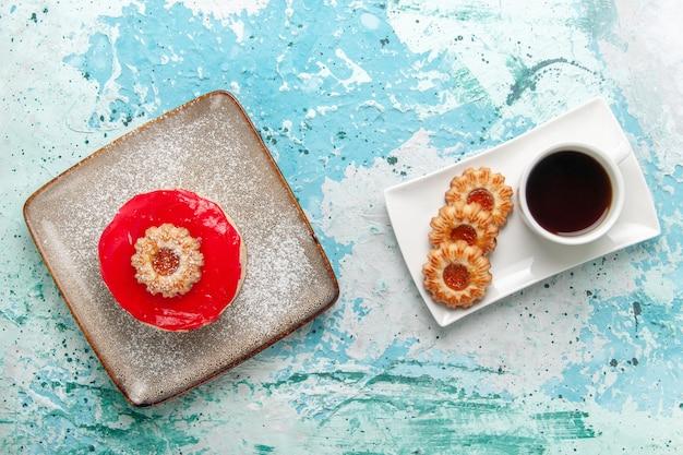Вид сверху маленький вкусный торт с красным кремом и печеньем на голубом фоне торт бисквит сладкий сахарный пирог чай