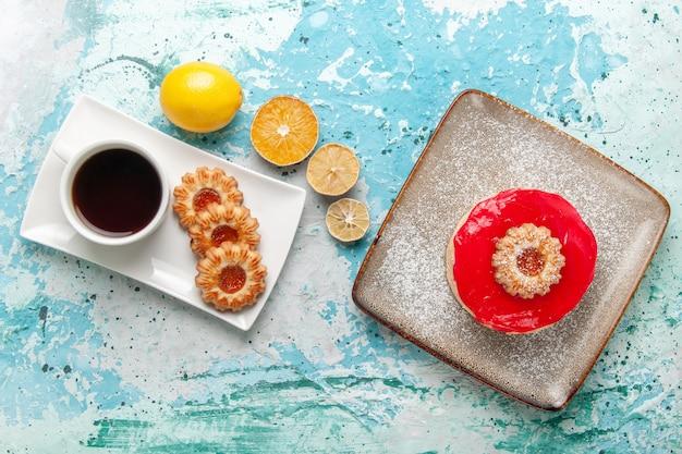 Vista dall'alto piccola deliziosa torta con crema rossa e biscotti sullo sfondo azzurro torta biscotto dolce torta di zucchero tè
