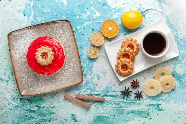 上面図水色の背景のケーキビスケット甘い砂糖パイティーに赤いクリーム色のお茶とクッキーと少しおいしいケーキ