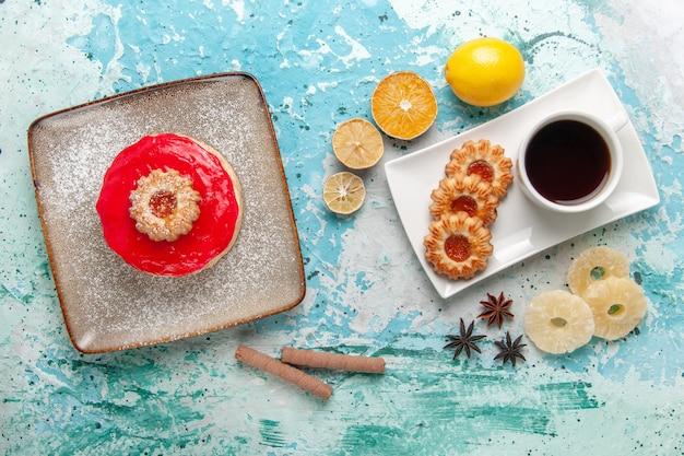 Vista dall'alto piccola deliziosa torta con crema rossa tazza di tè e biscotti su sfondo azzurro torta biscotto dolce torta di zucchero tè