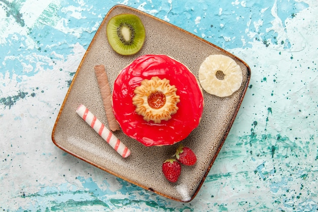 Vista dall'alto piccola deliziosa torta con crema rossa sulla superficie blu chiaro torta biscotto torta di zucchero dolce tè