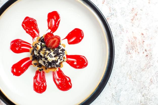 Вид сверху маленький вкусный торт с красной глазурью и шоколадной стружкой на белой поверхности бисквитного торта бисквитный сладкий пирог с печеньем