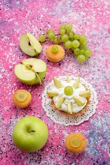 Вид сверху маленький вкусный торт с нарезанными фруктами и кремом на цветном столе, торт сладкого цвета сахара