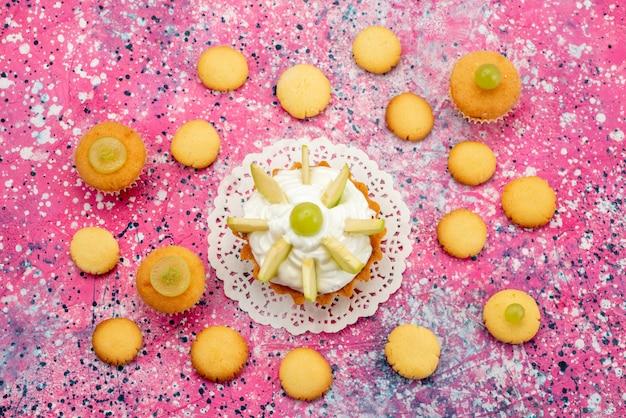 Vista dall'alto piccola torta deliziosa con biscotti di frutta a fette sulla foto a colori zucchero dolce torta colorata scrivania