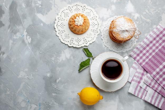 トップビューライトデスクケーキビスケット甘いビスケットクッキーの色にお茶のサンドイッチクッキーとサワーレモンの小さなおいしいケーキ