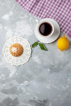 Vista dall'alto di una piccola torta deliziosa con tè e limone acido sulla scrivania leggera, biscotto torta biscotto dolce