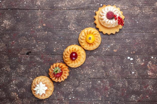 Vista dall'alto piccoli deliziosi dolci e biscotti con frutti di bosco sullo sfondo marrone biscotto foto bacca biscotto