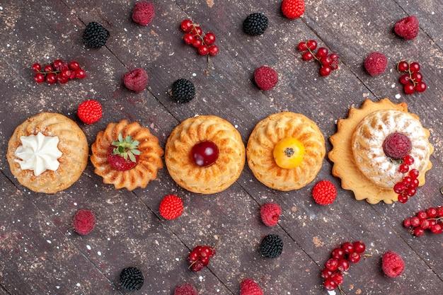 Vista dall'alto piccole torte e biscotti deliziosi con frutti di bosco diversi lungo tutto il biscotto della foto della bacca del biscotto della torta della scrivania marrone