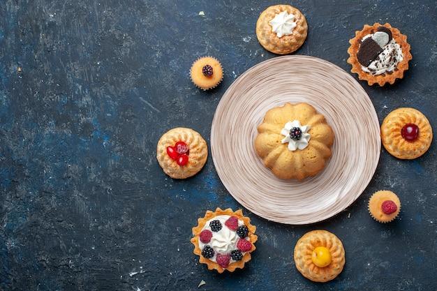 Vista dall'alto piccole deliziose torte diverse formate sulla torta di biscotti scuri da scrivania dolce cuocere